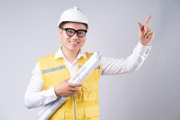 Asiatischer ingenieur, der zeichnung auf grau hält