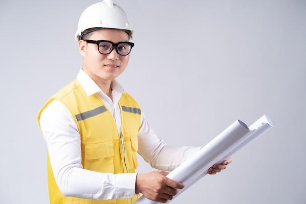Asiatischer ingenieur, der zeichnung auf grau liest