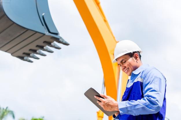 Asiatischer ingenieur prüft pläne auf der baustelle
