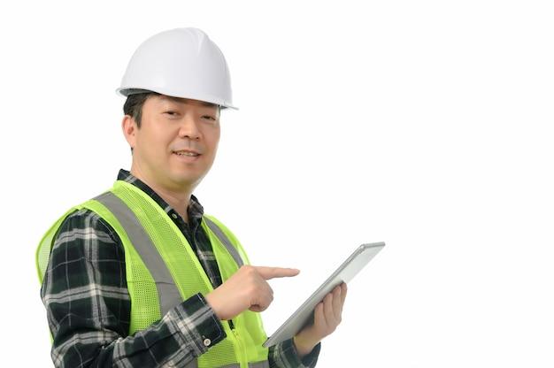 Asiatischer ingenieur von mittlerem alter, der tablet-pc auf einem weißen hintergrund verwendet.