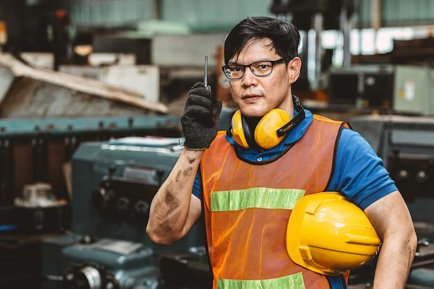 Asiatischer ingenieurarbeiter mit schutzanzug stellte harte arbeit in der fabrikhandgriffkommunikationsfunk schauen kamera und lächeln ein.
