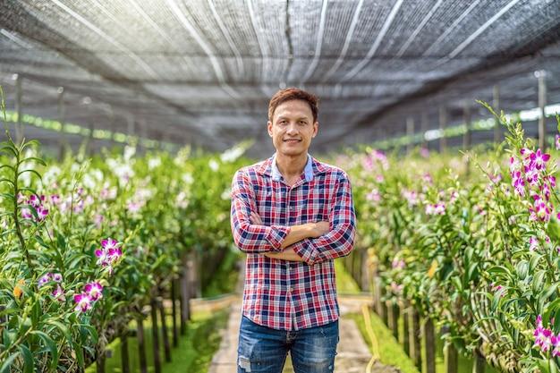 Asiatischer inhaber des porträts des orchideengartenarbeitbauernhofes