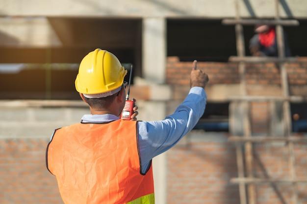 Asiatischer inspektor, der die struktur der neuen immobilie überprüft und zur überprüfung das haus in der zwischenablage zur kenntnis nimmt, bevor es an den kunden verkauft wird