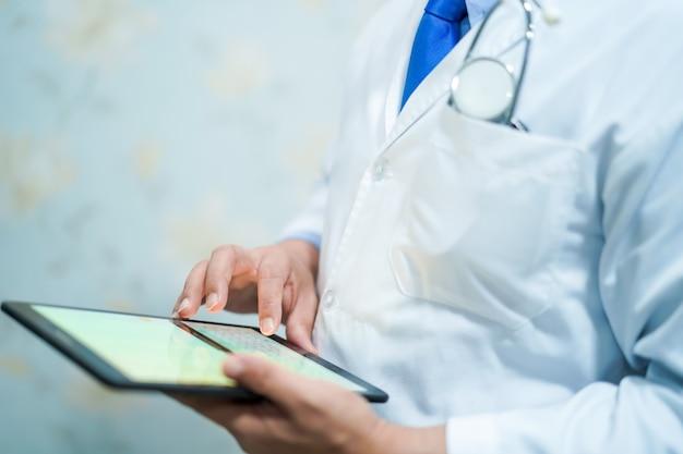 Asiatischer intelligenter manndoktor, der digitale tablettentechnologie hält, um wissen zu suchen.