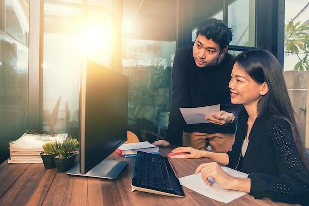 Asiatischer jüngerer freiberuflicher mann und frau, die an computer im innenministerium arbeitet