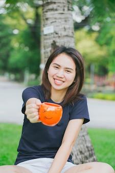 Asiatischer jugendlich grifflächelnbecher im grünen park. happy drink kaffee-konzept.