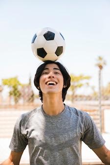 Asiatischer jugendlich student, der fußball auf kopf hält