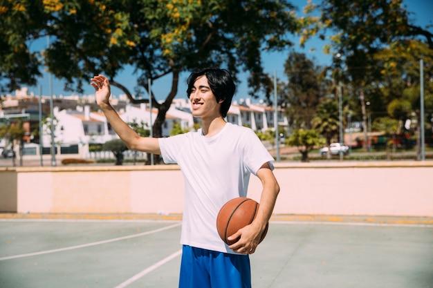 Asiatischer jugendlich student, der grußgeste am gericht zeigt