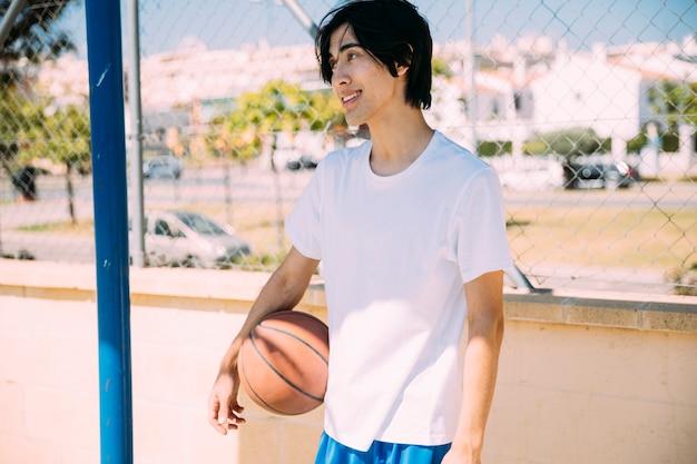 Asiatischer jugendlich student, der mit basketball steht