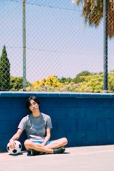 Asiatischer jugendlich student, der neben sportplatzzaun sitzt
