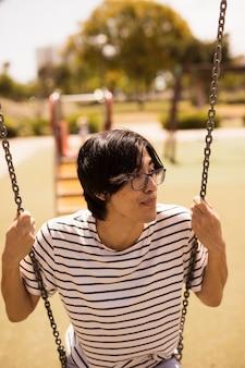Asiatischer jugendlicher, der auf schwingen sitzt
