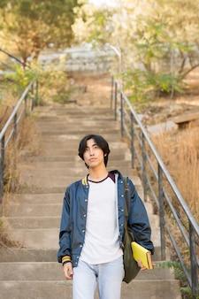 Asiatischer jugendlicher, der in der hand treppe mit buch hinuntergeht