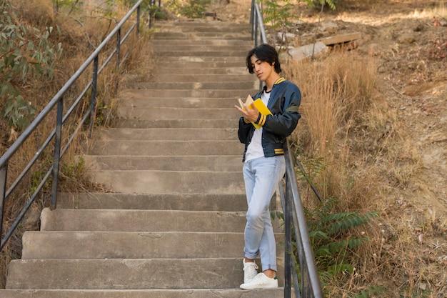 Asiatischer jugendlicher, der mit buch auf treppen steht