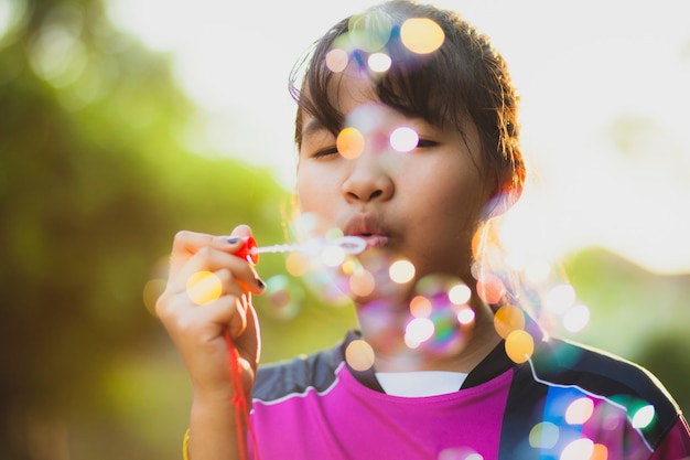 Asiatischer jugendlicher, der mit suppenblase gegen schönes sonnenlicht sich entspannt