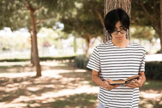 Asiatischer jugendstudent mit geöffnetem buch