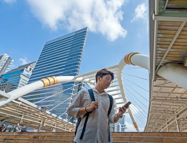 Asiatischer jugendstudent rucksack auf äußeren schritten unter verwendung des handys