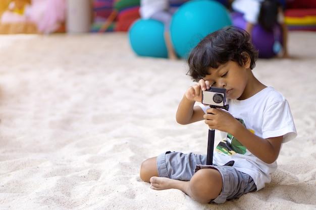 Asiatischer junge, der aktionskamera verwendet, um ein foto oder ein video zu machen