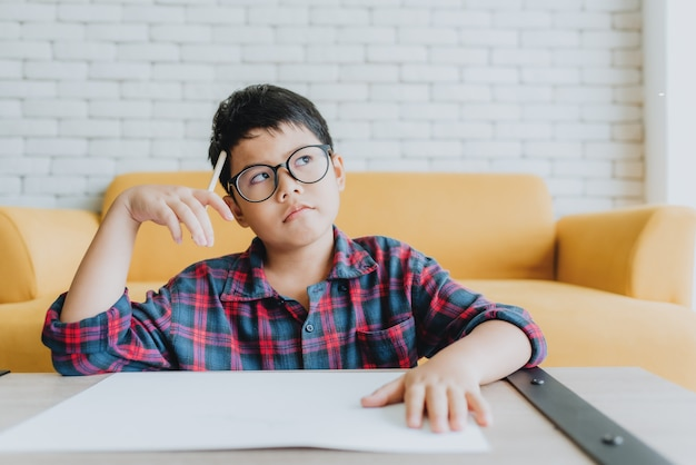 Asiatischer junge, der an etwas denkt