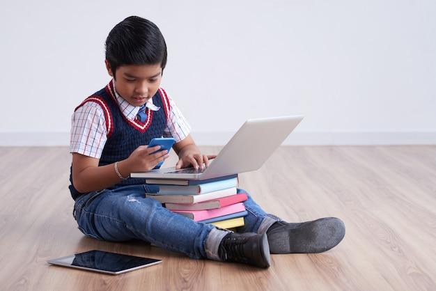 Asiatischer junge, der auf boden mit tablette und laptop auf staplungsbüchern sitzt und smartphone verwendet