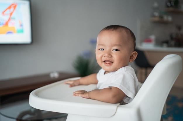 Asiatischer junge, der auf hochstuhl sitzt