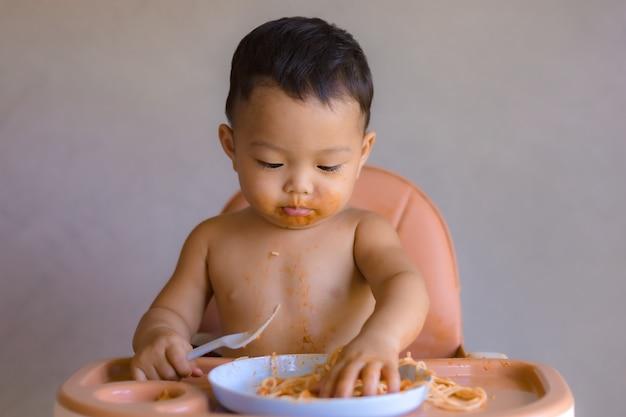Asiatischer junge, der auf hohem kinderstuhl isst.