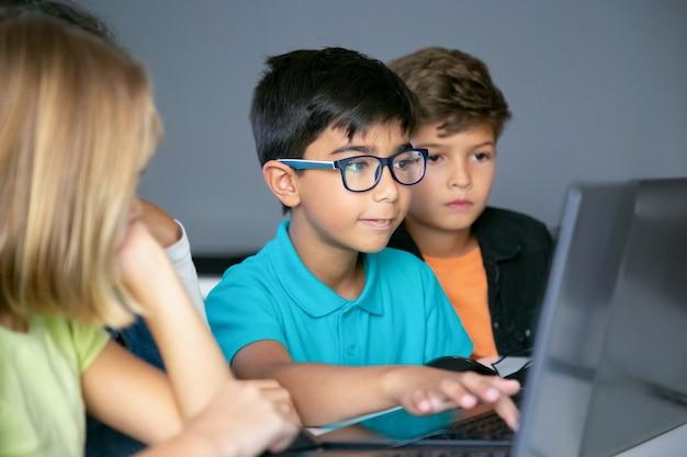 Asiatischer junge, der auf laptoptastatur und klassenkameraden tippt, die am tisch sitzen, ihn beobachten und aufgabe zusammen erledigen