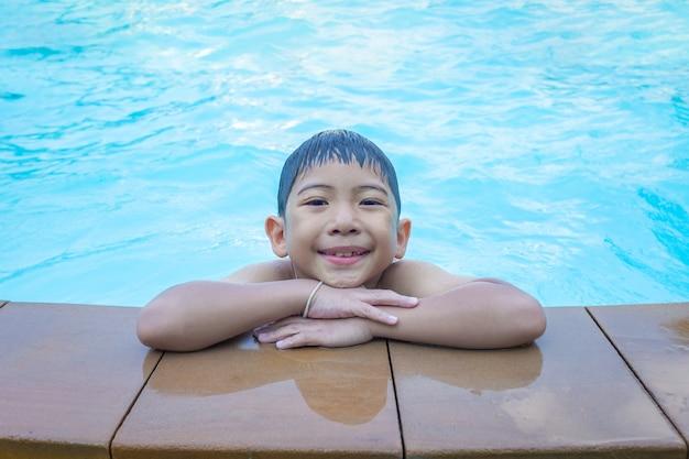Asiatischer junge, der auf rand des swimmingpoolblaus lächelt