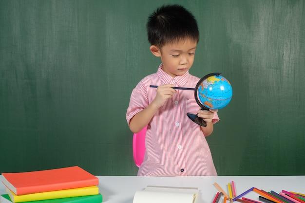 Asiatischer junge, der auf weltkarte im kreidebrettraum zeigt.