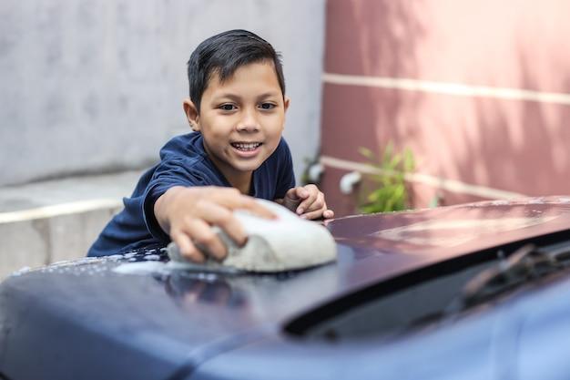 Asiatischer junge, der auto wäscht, indem er die motorhaube mit schwamm und seifenschaum reibt