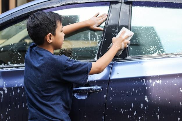 Asiatischer junge, der autofenster mit schwamm und seifenschaum wäscht