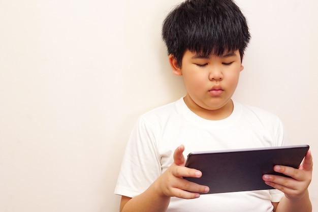 Asiatischer junge, der digitale tablette mit einem weißen hintergrund spielt.