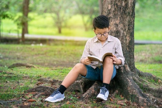 Asiatischer junge, der durch baumstamm im park und im lesebuch sitzt