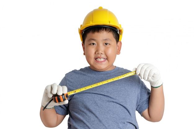 Asiatischer junge, der einen gelben helm trägt und maßband hält