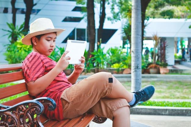 Asiatischer junge, der einen hut sitzt auf einem stuhl spielt eine tablette trägt