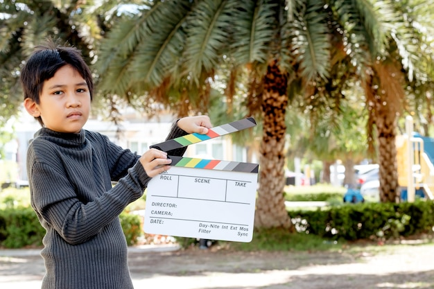 Asiatischer junge, der filmschieferfarbenbrett für filmkino- und fernsehindustrie hält