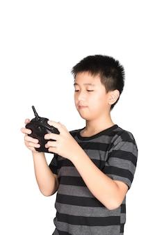 Asiatischer junge, der funkfernsteuerungshörer für spielzeug hält