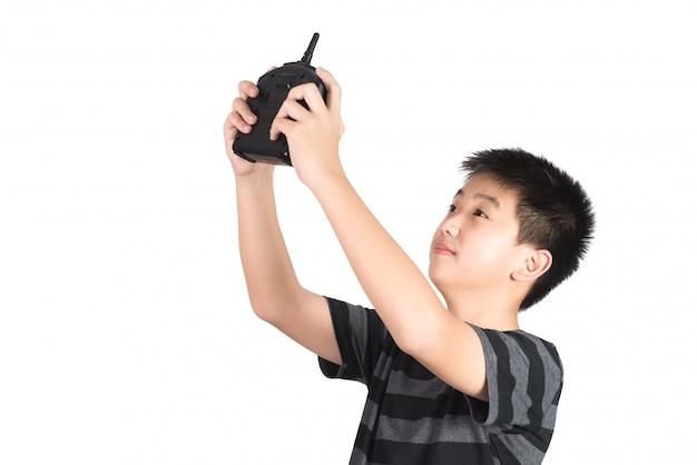 Asiatischer junge, der funkfernsteuerungshörer hält