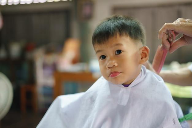 Asiatischer junge, der haar vom friseur schneiden lässt