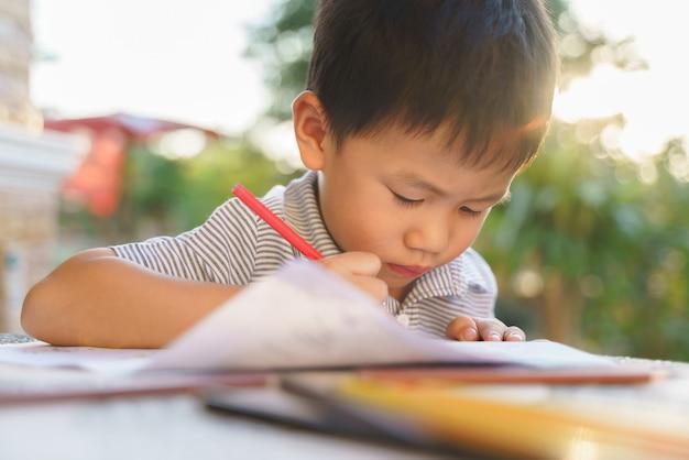 Asiatischer junge, der hausaufgabenbild malt