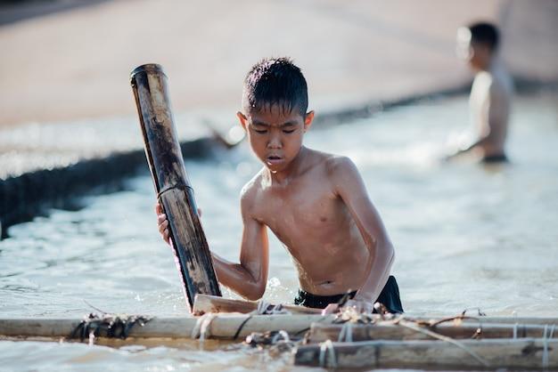 Asiatischer junge, der hölzernes boot im fluss spielt