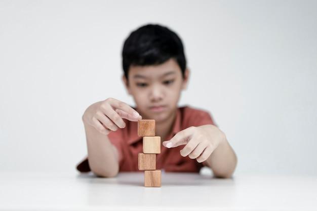 Asiatischer junge, der holzwürfel, bildungskonzepte und das lernen in einer neuen normalität wählt.