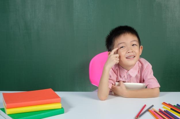 Asiatischer junge, der im kreidebrettraum lächelt und denkt