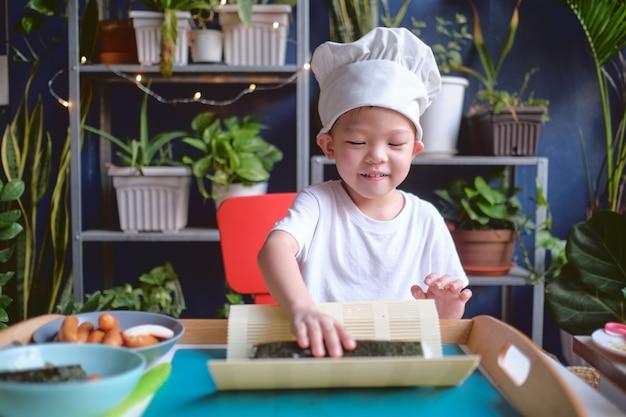 Asiatischer junge, der kochmütze und schürze beim kochen trägt