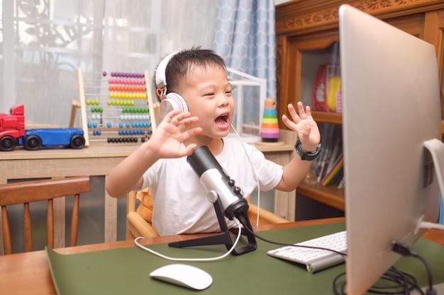 Asiatischer junge, der kopfhörer mit mikrofon mit computer trägt, der videoanruf zu verwandten zu hause macht oder vlog für social-media-kanal macht