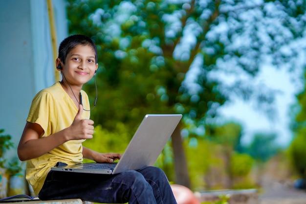 Asiatischer junge, der laptop-computer für online-homeschooling während der heimquarantäne verwendet. homeschooling, online-studium, heimquarantäne, online-lernen, corona-virus oder bildungstechnologiekonzept