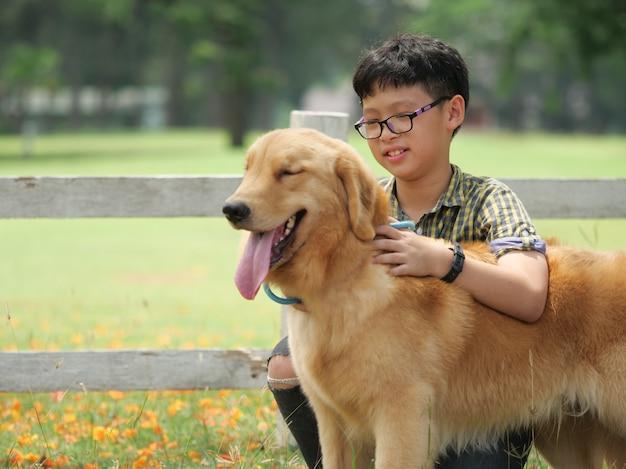Asiatischer junge, der mit hündchen goldenem retreiver im park spielt