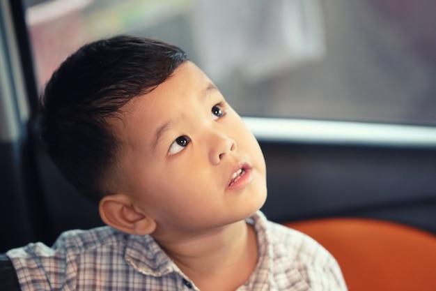 Asiatischer junge, der mit misstrauen in einem auto beginnt.