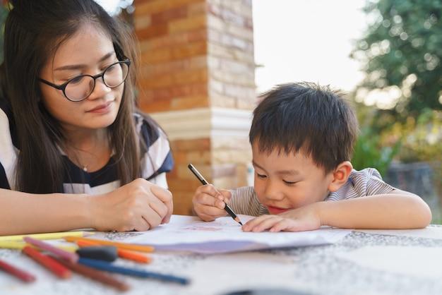 Asiatischer junge, der mit seiner mutter zeichnet und malt