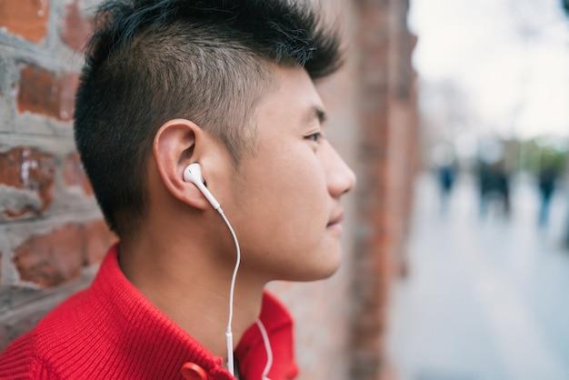 Asiatischer junge, der musik mit kopfhörern hört.