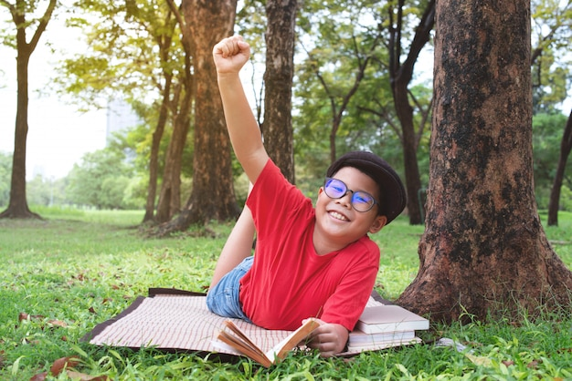 Asiatischer junge, der öffentlich unter dem großen park des baums, mit der glücklichen ausdruckhand oben liegt